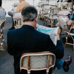 Leggere il giornale in un caffè a Parigi